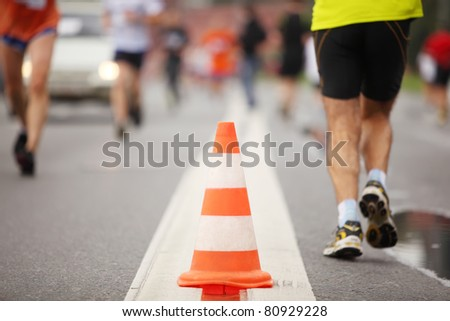 Big color cone on road between running people, close-up view - stock photo