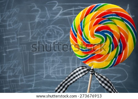 Big colorful lollipop with checkered ribbon. - stock photo