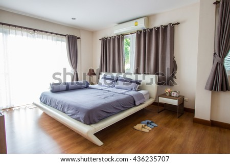 Big comfortable double bed in modern bedroom - stock photo