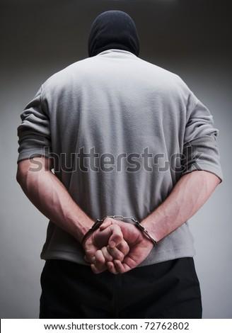 Big criminal locked in handcuffs. Terrorist in balaclava - stock photo