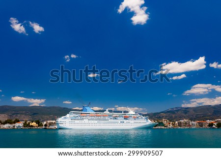 Big cruise ship anchored in port against a blue sky and clouds in Greece - stock photo