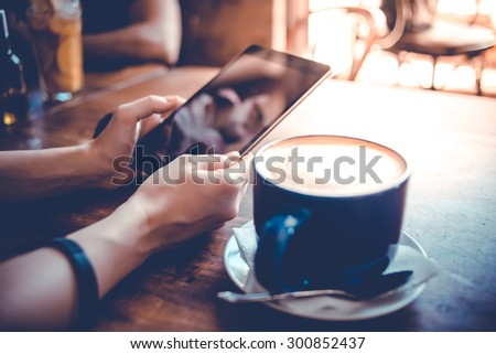 Big cup of coffee and hands holding tablet in cafe. Toned image - stock photo