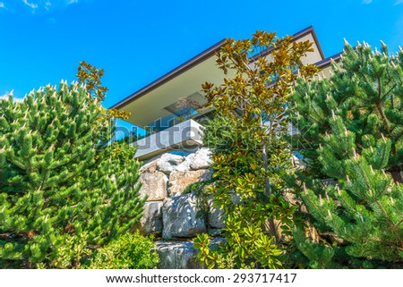 Big custom built luxury modern house on the rocks, cliff with nicely landscaped front yard in the residential neighborhood of Vancouver, Canada. Vertical. - stock photo