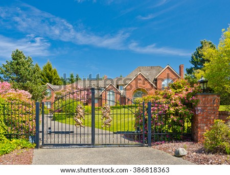 Big custom made luxury house behind the gates with nicely trimmed and landscaped front yard in the suburbs of Vancouver, Canada. - stock photo