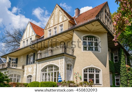 Big custom made luxury house with a brown tile roof and green hedges - a typical traditional austrian (german) building in a residential neighborhood. - stock photo