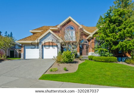 Big custom made luxury house with double doors garage and nicely trimmed and landscaped front yard and paved driveway in the suburbs of Vancouver, Canada. - stock photo