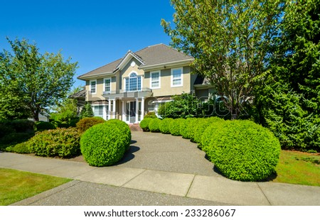 Big custom made luxury house with nicely landscaped and trimmed front yard and paved doorway in the suburbs of Vancouver, Canada. - stock photo