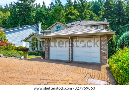 Big custom made luxury house with nicely landscaped and trimmed front yard and paved driveway to garage in the suburbs of Vancouver, Canada. - stock photo