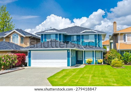 Big custom made luxury house with nicely landscaped front yard and driveway to garage in the suburbs of Vancouver, Canada. - stock photo