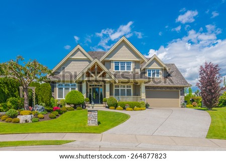 Big custom made luxury house with nicely landscaped front yard and driveway to garage in the suburb of Vancouver, Canada. - stock photo