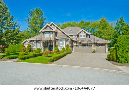 Big custom made luxury house with nicely landscaped front yard, triple doors garage and long and wide driveway in the suburbs of Vancouver, Canada. - stock photo