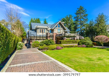 Big custom made luxury house with nicely paved driveway and with nicely trimmed and landscaped front yard in the suburbs of Vancouver, Canada. - stock photo