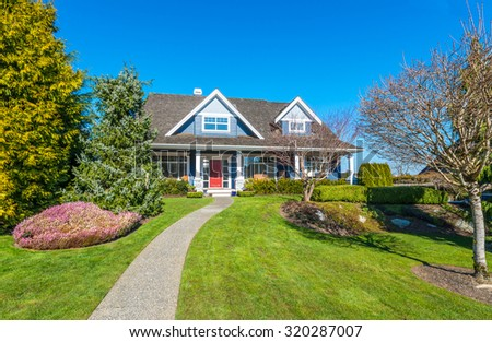 Big custom made luxury house with nicely trimmed and landscaped front yard and doorway in the suburbs of Vancouver, Canada. - stock photo