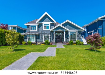 Big custom made luxury house with nicely trimmed and landscaped front yard and long doorway  in the suburb of Vancouver, Canada. - stock photo