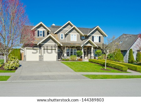 Big custom made luxury house with two doors garage, long driveway and  nicely trimmed and landscaped front yard lawn in the suburbs of Vancouver, Canada. - stock photo