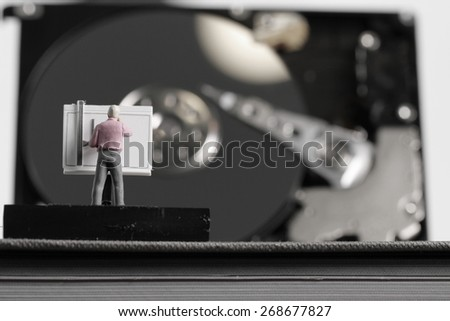Big data concept-miniature engineer working with drafting table with open hard disk background - stock photo