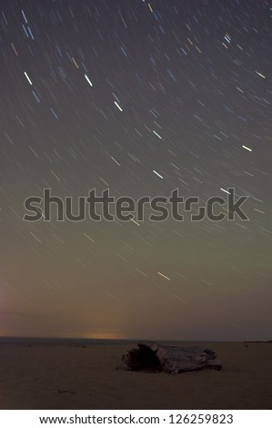 Big dipper and milky way in long exposure on beach with driftwood in foreground - stock photo