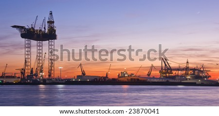 Big drilling platform in repair in the harbour at sunset - stock photo