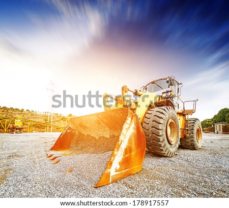 Big excavator on new construction site, in the background the blue sky and sun - stock photo