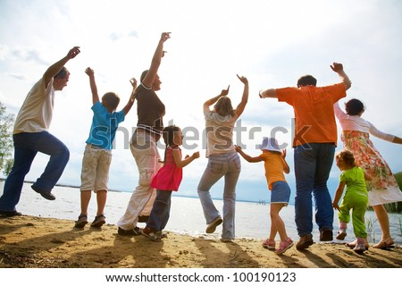 Big family from  adults and children dancing on the beach - stock photo