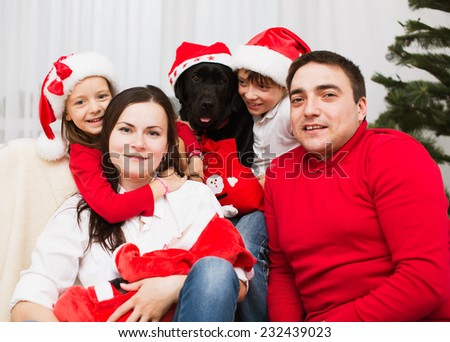 Big Family. Parents with three children and dog labrador in santa hats - stock photo