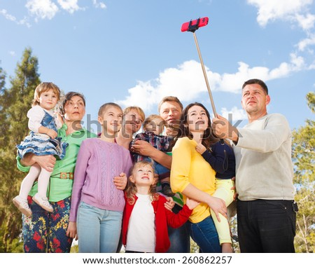 Big Family taking selfie with mobile phone on a selfie stick. - stock photo
