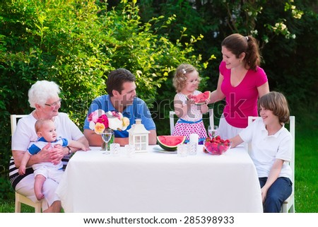 Big family with children have lunch outdoors. Parents with 3 kids and grandmother eat in the garden. Picnic for mother, father, baby boy, toddler girl and teenager child. Generations and retirement. - stock photo