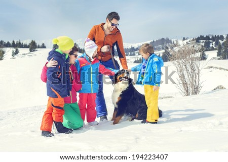 big family with dog having fun in the snow - stock photo