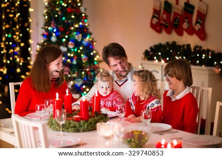 Big family with three children celebrating Christmas at home. Festive dinner at fireplace and Xmas tree. Parent and kids eating at fire place in decorated room. Child lighting advent wreath candle - stock photo