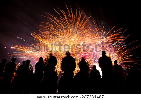 Big fireworks with silhouettes of people watching it - stock photo