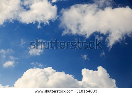 Big fluffy clouds in blue sky - stock photo