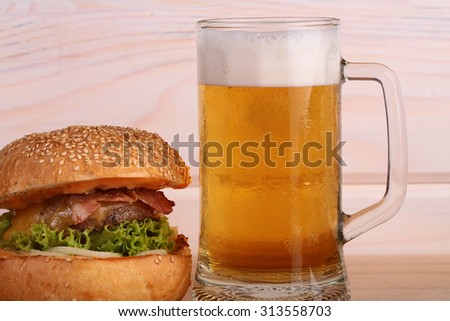 Big fresh tasty burger of green lettuce meat cutlet tomato and white bread bun with sesame seeds near and glass of light beer with froth on octoberfest holiday on wooden background, horizontal picture - stock photo