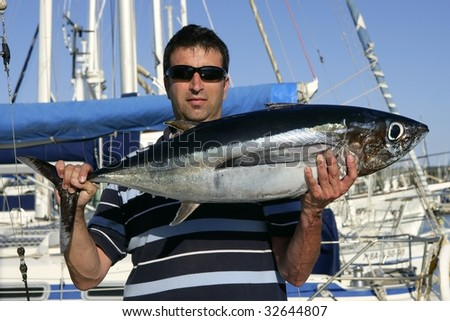 Big game fisherman with saltwater tuna catch in his hands - stock photo