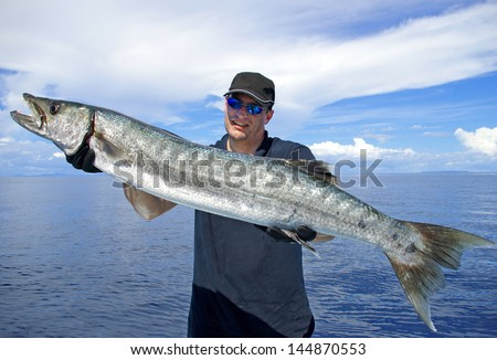 Big game fishing. Lucky  fisherman holding a giant barracuda - stock photo