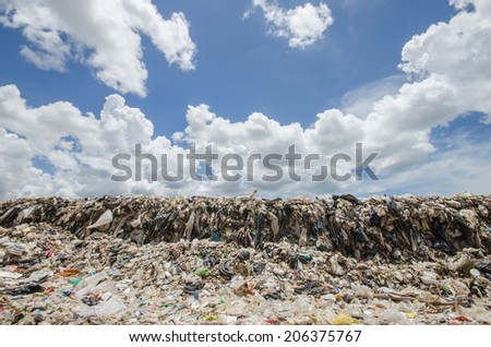 big garbage heap under blue sky - stock photo