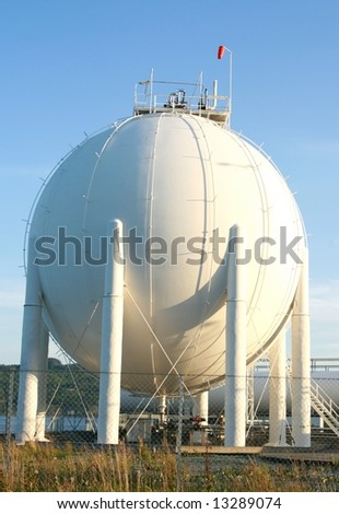 Big gas container against the blue sky - stock photo