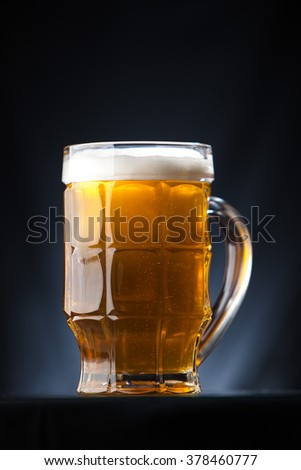 Big glass of beer over a dark background - stock photo