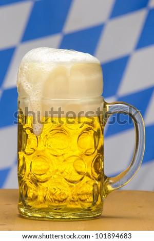 big glass of 1 liter german bavarian beer in front of bavarian flag - stock photo