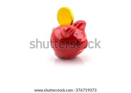 Big gold coin into a red pig bank isolated on white background - stock photo
