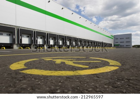Big gray distribution warehouse building with green stripe - stock photo