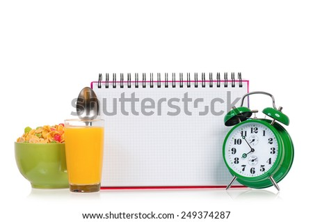 Big green alarm clock with breakfast and blank notebook, isolated on white background - stock photo