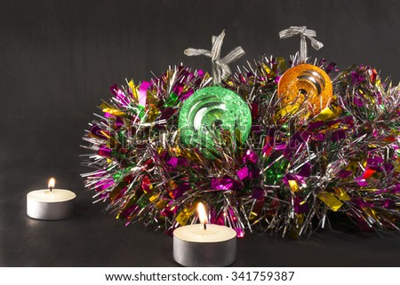 Big green and orange carved mirror xmas balls with a candles on a background of tinsel - stock photo