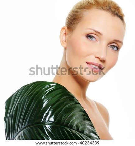 Big green leaf covering the  woman's body with  fresh clear skin - stock photo