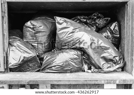 Big green trash have full of garbage bag on black and white background - stock photo