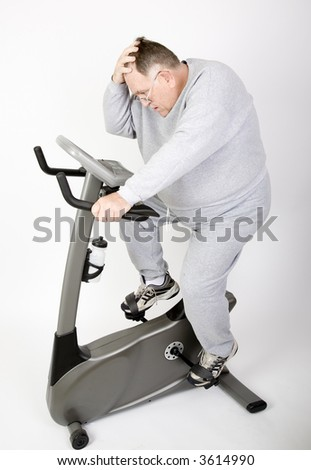 Big Guy Working off the fat on the exercise bike - stock photo