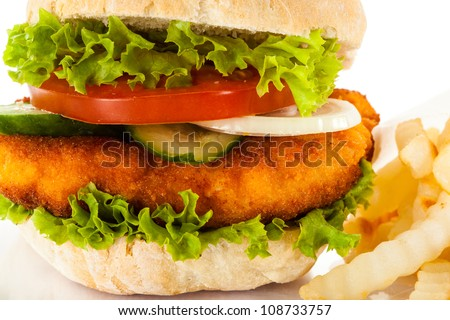 Big hamburger, French fries and vegetables on white background - stock photo