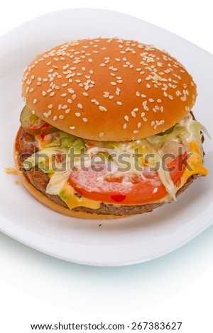 """Big hamburger from a natural whole beef with a slice of cheese """"cheddar"""" on caramelized bun, seasoned with mustard, ketchup, onions, two slices of pickles, fresh lettuce, a slice of fresh tomato   - stock photo"""