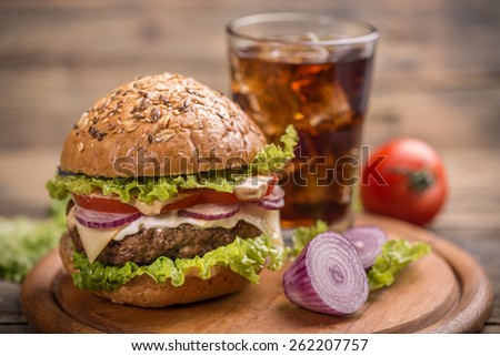 Big hamburger on wooden chopping board - stock photo