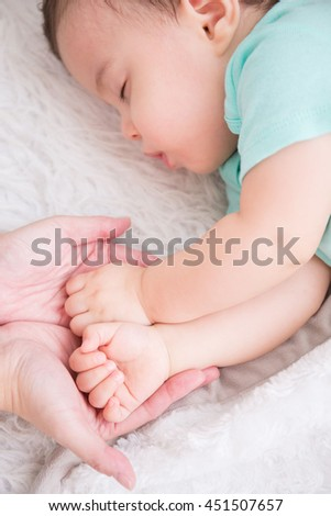 big hand hold cute baby fist and baby sleep on the white bed in bedroom, caucasian - stock photo
