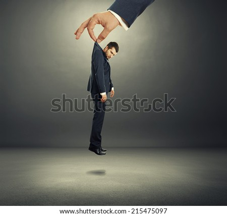big hand holding small discontented businessman in dark room - stock photo
